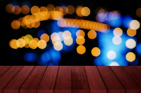 empty red wooden wooden terrace with abstract night light bokeh of night festival in garden, blurred background, copy space for display of product or object presentation, vintage color tone