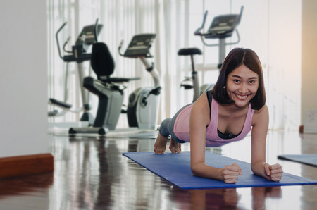 young pretty asian woman slim body smiling doing plank exercise on floor with yoga mat after workout in fitness gym at morning, good health, motivation, healthy lifestyle, exercise and workout concept Stock Photo - 106624194