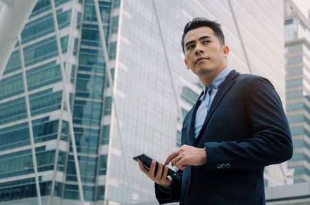young handsome asian business man wearing modern black suit reading information about finance news with mobile smart phone in building city background, network technology, internet, successful concept Stock Photo