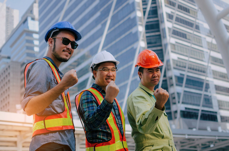 yeah, finally we did it, group of engineer, technician and architect screaming showing their strong hands together standing in modern city building background, construction site and industry concept Stock Photo