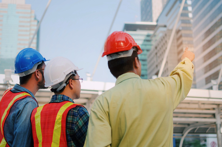 back view group of engineer, technician and architect with safety helmet planning about building plan with blueprint in modern city building background, construction site, industry and worker concept