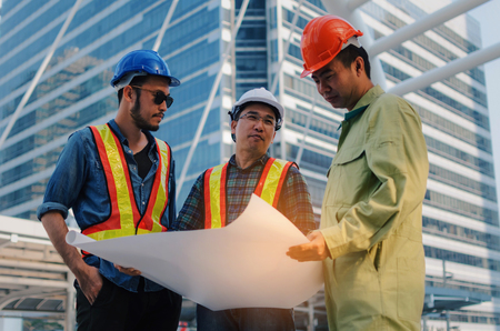 group of engineer, technician and architect with safety helmet planning about building plan with blueprint in modern city building background, construction site, business, industry and worker concept Stock Photo