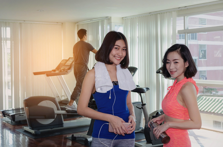 couple smiling asian young woman slim body with towel in fitness gym at morning with people on machine bicycle background, bodybuilder, healthy lifestyle, exercise, workout, sport training concept