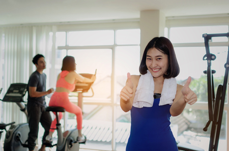 young happy asian woman slim body with towel showing thumbs up in fitness gym with people on machine bicycle background, bodybuilder, healthy lifestyle, exercise, workout and sport training concept Stock Photo