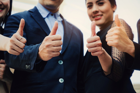 close up of hand group of young business people team in suit showing thumbs up as like sign together in the city, successful, support, meeting, partner, teamwork, community and connection concept