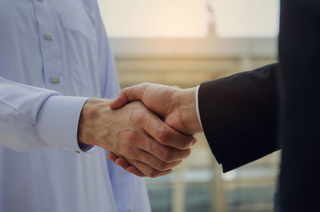 Deal. close up hand of young Arabian man in white suit handshake with business man in black suit after finishing up meeting, partnership, teamwork, community, connection financial, investment concept