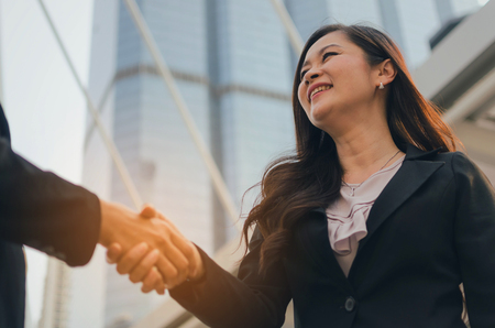 business asian woman in modern black suit handshake with people after finishing up meeting in city, partnership, teamwork, community, connection financial and investment concept