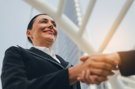 business caucasian woman in modern black suit handshake with people after finishing up meeting in city, partnership, teamwork, community, connection financial and investment concept