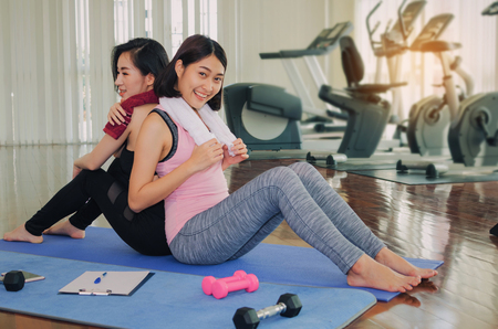 two happy asian young woman slim body with towel sitting with back to each other on yoga mat in fitness gym at morning, bodybuilder, healthy lifestyle, exercise, workout, sport training concept