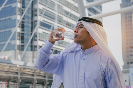 young handsome Arabian man in white suit standing and drinking natural water from bottle for refresh yourself with modern city background, lifestyle, healthy, summer concept