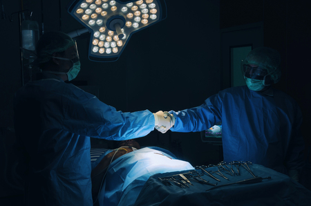 Doctor shaking hands with Assistant after surgeons work for rescue patient in operation room at hospital, emergency case, surgery, medical technology, health care cancer and disease treatment concept Stock Photo - 107720827