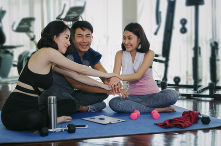 young sport people team planning to reach their goal and doing high five together sitting on yoga mat in fitness gym, exercise, training, workout, partnership, success and teamwork concept Stock Photo