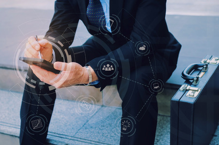 hand of business man wearing modern black suit using mobile smart phone and briefcase sitting on walkway in city with graphic network diagram, technology communication, internet and financial concept