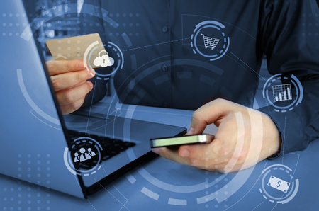 young man entering security code with smart phone and paying with credit card and laptop computer on desk at home office with graphic icon diagram, payment and shopping online, technology concept