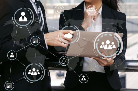 business man and woman in suit talking and reading information about finance news in laptop computer with virtual innovation, investment, network technology, internet and teamwork concept Stock Photo