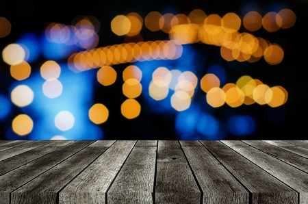 empty grey wooden terrace with abstract night light bokeh of night festival in garden, blurred background, copy space for display of product or object presentation, vintage color tone