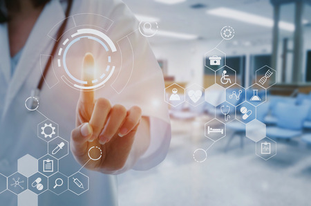 female doctor with stethoscope hand pointing touching data digital icon hologram with blurred image of lobby for waiting in hospital background, innovation, medical, future and technology concept. Stock Photo
