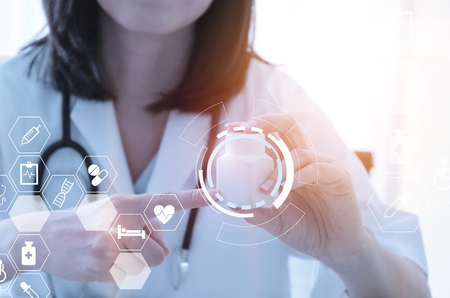 young female doctor or pharmacist with stethoscope holding or showing bottle of pills in hand at hospital with data digital icon hologram, innovation, medical, medicine, future technology concept