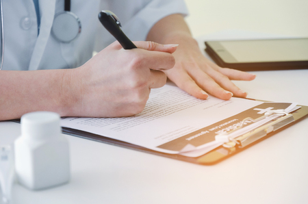 young female doctor or pharmacist with stethoscope writing prescription on clipboard  and bottle of pills on desk in hospital, health care, medical, medicine, pharmacy and insurance concept