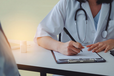 young female doctor or pharmacist with stethoscope writing prescription on clipboard and bottle of pills on desk with patient in hospital, health care, medical, medicine, pharmacy, insurance concept Stock Photo