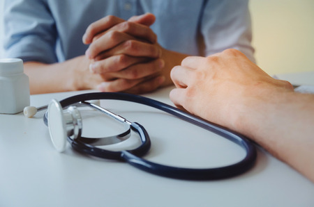 close up of doctor and patient sitting with stethoscope and bottle of pills on desk in hospital, health care, medical, medicine, pharmacy and insurance concept