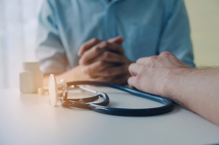 close up of hand of doctor and suffering patient sitting with stethoscope and bottle of pills on desk in hospital, encouragement, health care, medical, medicine, pharmacy and insurance concept Stock Photo