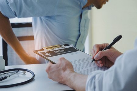young business man suffering from backache meet doctor writing prescription on clipboard with stethoscope on desk in hospital, office syndrome, health care, medical, medicine, pharmacy concept Stock Photo