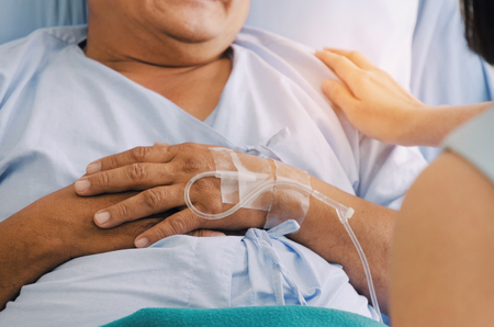 close up caring daughter hand on patient shoulder and keeping old patient hand lying in bed at hospital for encouragement, elderly people, family, medical, health care, cheering and support concept Stock Photo