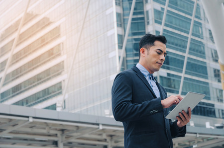 young asian investor business man in modern suit standing and working about finance on digital mobile tablet in office building, smart technology, investment, stock market and global business concept Stock Photo