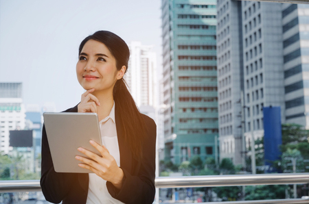 beautiful smiling young asian investor business woman wearing modern black suit thinking and looking up with mobile tablet in modern city, investment,   network technology, internet, digital concept