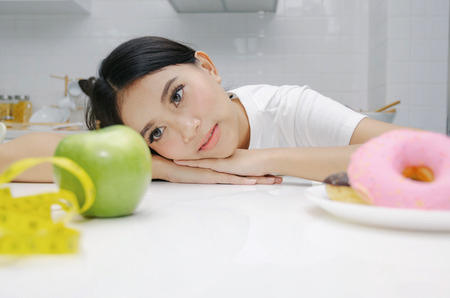 portrait of confused young asian woman choosing between fresh green apple and donut on table in kitchen, healthy food, clean eating, dieting, unhealthy food, good health care and weigh loss concept Stock Photo