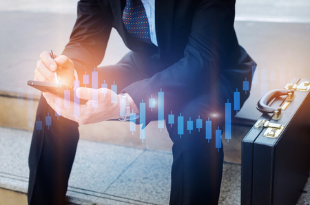 young investor or business man and using mobile phone with graphic candle stick graph chart Stock Photo