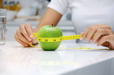 close up young woman hand holding measuring tape around fresh green apple on white table in kitchen