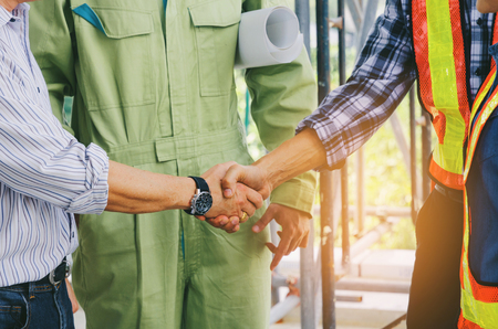 midsection of team of engineer and technician contractor shaking hands after finishing up business meeting