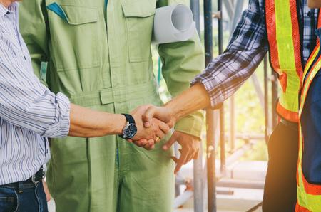 Mittelteil des Teams von Ingenieuren und Technikern, die sich nach Abschluss des Geschäftstreffens die Hände schütteln