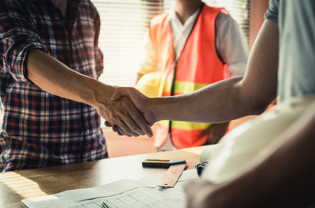 team of construction worker shaking hands with customer after finishing up business meeting