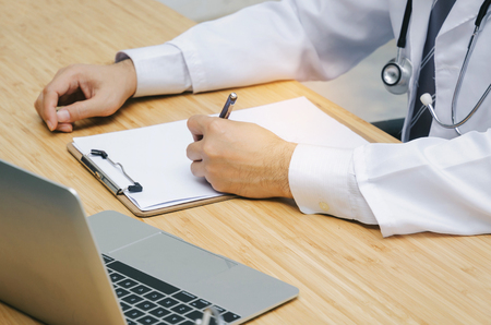 doctor or pharmacist with stethoscope on neck working with laptop computer Stock Photo