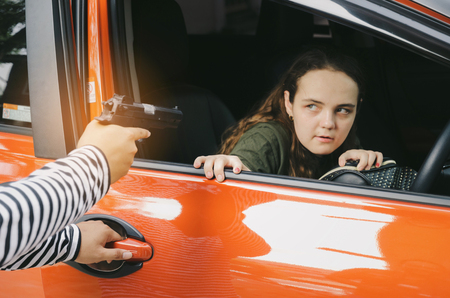 thief or robber in black and white jacket and masked hood with gun threatens young caucasian woman Stock Photo