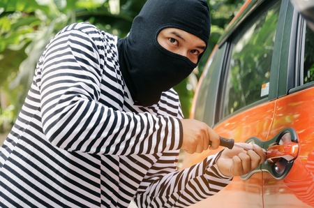 thief in black and white jacket using screwdriver to open orange car door to stealing a car on street in big city, break into the car crime robber and steal concept Stock Photo