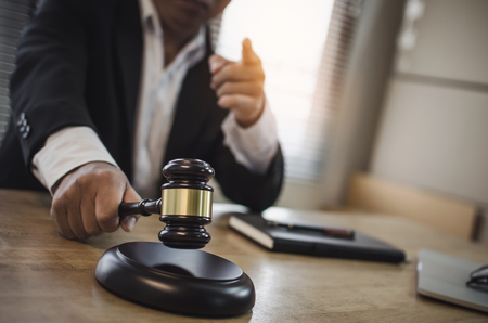 justice lawyer in black suit pointing finger and knocking wooden judge gavel with documents on workplace desk in courtroom office, occupation, business, justice law and legal service concept