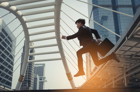 happy young investor business man holding briefcase running fast and jumping in the air with modern building in city background, rush hour, celebrating, investment and company success concept