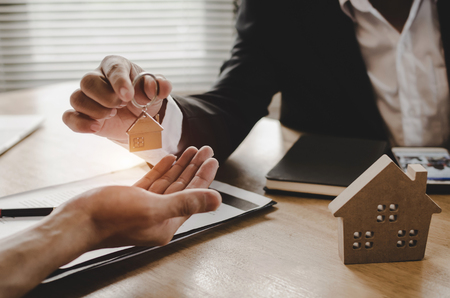 Immobilienmaklermanager, der dem Kunden den Hausschlüssel gibt, nachdem er den Vertrag für den Kauf eines Hauses im Immobilienmaklerbüro, Investitionen, Wohnungsbaudarlehensvertrag, Hauskauf, Immobilien- und Versicherungskonzept unterzeichnet hat Standard-Bild