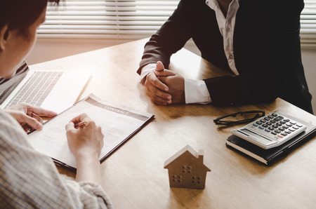 Realtor - young man customer signing contract for buying house with real estate broker in suit at estate agent office, investment, home loan contract, buying house, real estate and insurance concept
