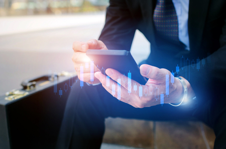 young investor or business man using mobile phone with graphic candle stick graph chart of stock market investment trading for Forex trading, digital technology, investment and global business concept