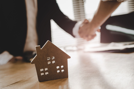 real estate broker manager hand shake to customer after signing contract for buying house in estate agent office behind House model, investment, home loan contract, buy and sell house concept Standard-Bild - 115808628