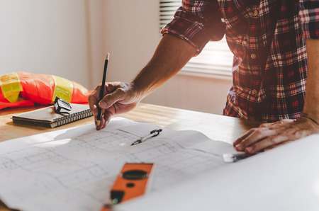 hand professional architect, engineer or interior hands drawing with blueprint on workplace desk in office center at construction site, contractor, construction, engineering and business concept