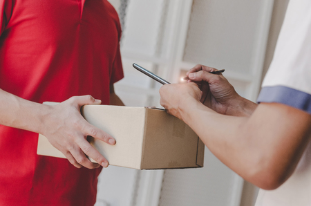 home delivery service man in red uniform and young man customer appending signature in digital mobile phone receiving parcel post box from courier at home, express delivery and online shopping concept