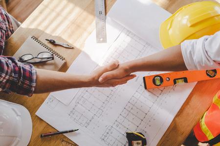 vue de dessus de l'équipe de travailleurs de la construction serrer la main de l'entrepreneur après avoir terminé la réunion d'affaires pour saluer le contrat de projet de démarrage dans la construction du chantier de construction, travail d'équipe, partenariat, concept de l'industrie Banque d'images