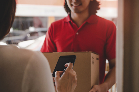 home delivery service man in red uniform and young woman customer appending signature in digital mobile phone receiving parcel post box from courier at home, express delivery, online shopping concept