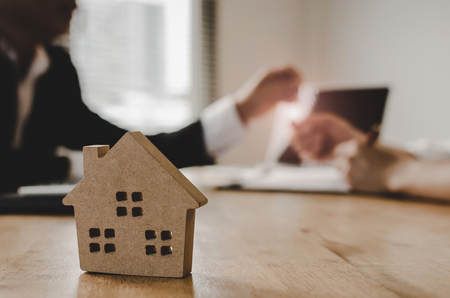 real estate broker manager giving keys to customer after signing contract for buying house in estate agent office behind House model, investment, home loan contract, realtor, buy, sell house concept